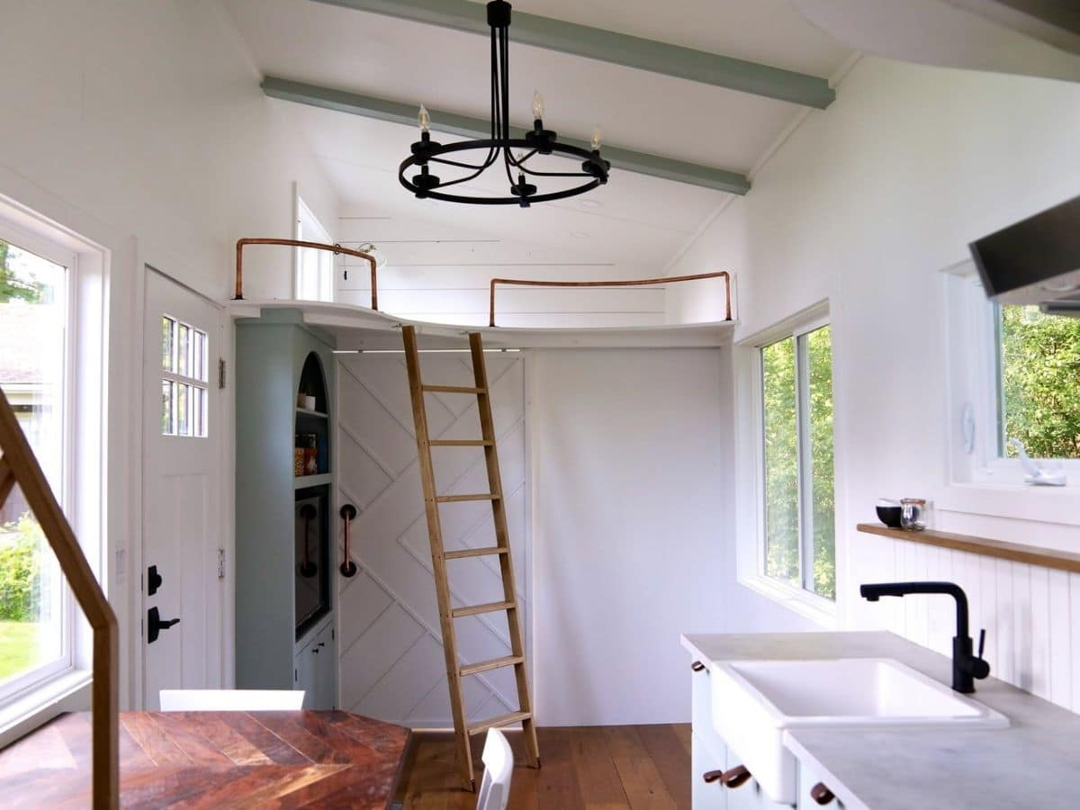 bedroom door closed with ladder in front of green cabinet with tv