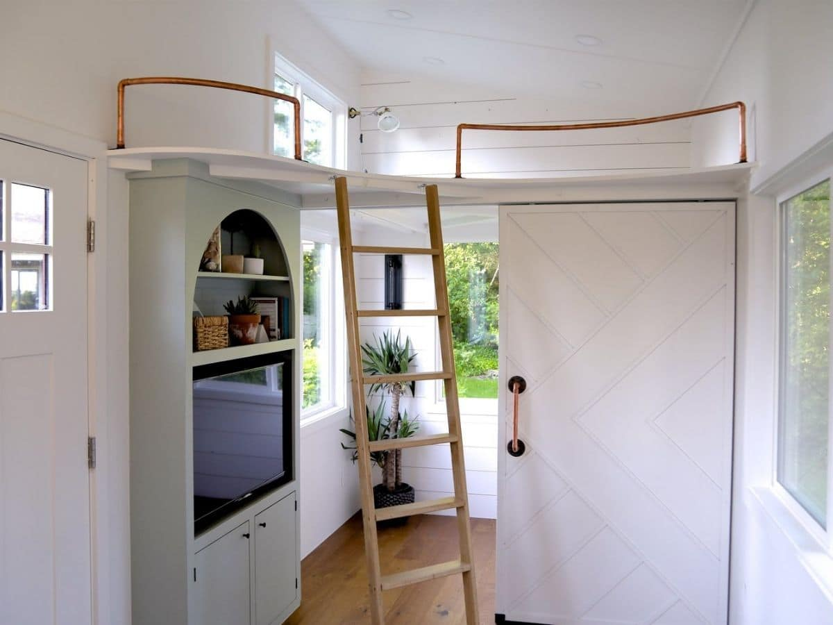 green cabinet on left next to ladder to loft with door open to bedroom
