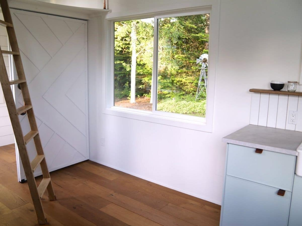 green cabinet against wall by window and ladder
