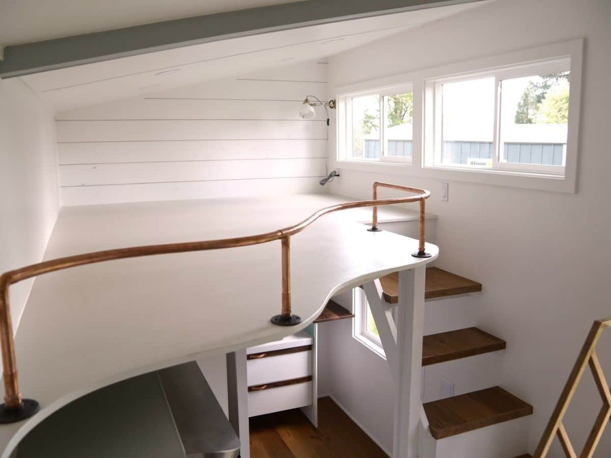 open loft above stairs with curved edge and railing