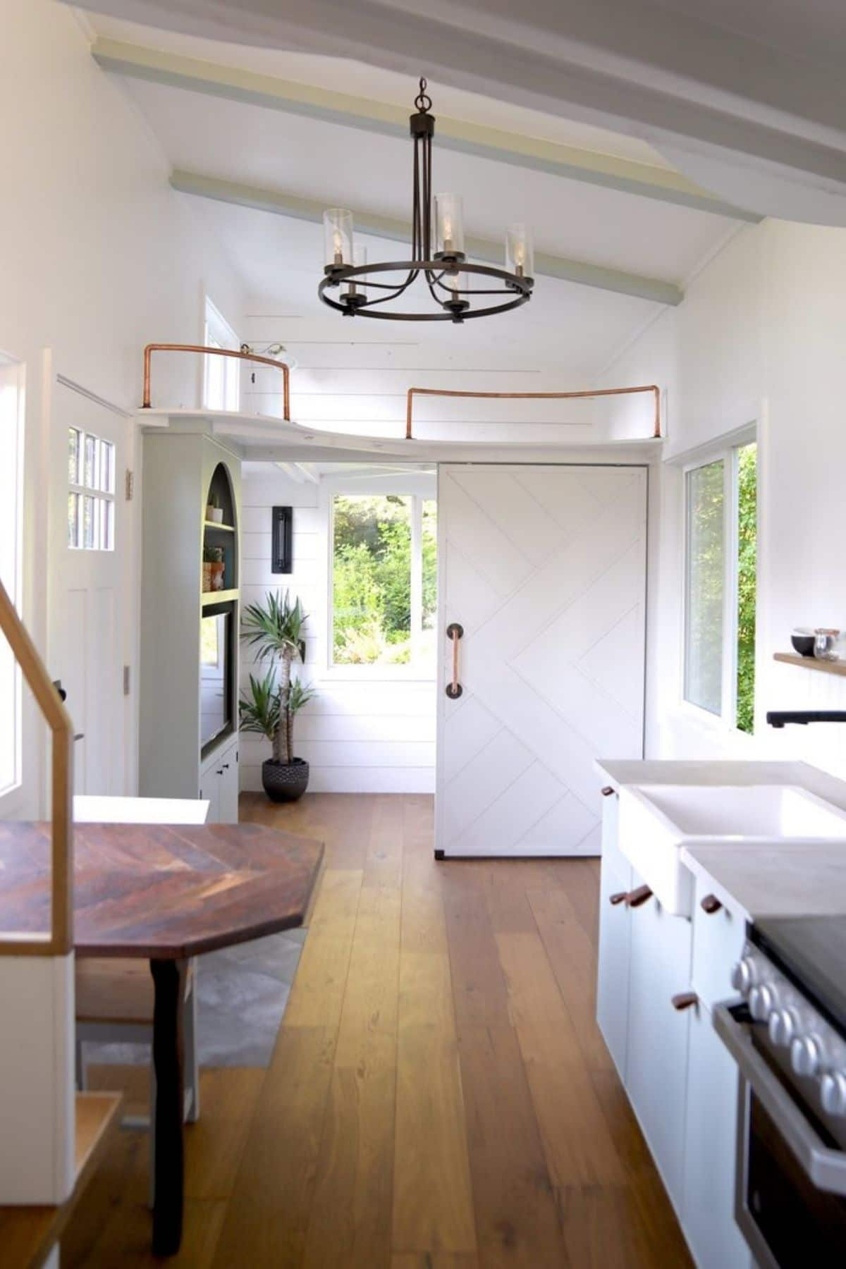 view into private bedroom from kitchen with loft in background and sink in foreground