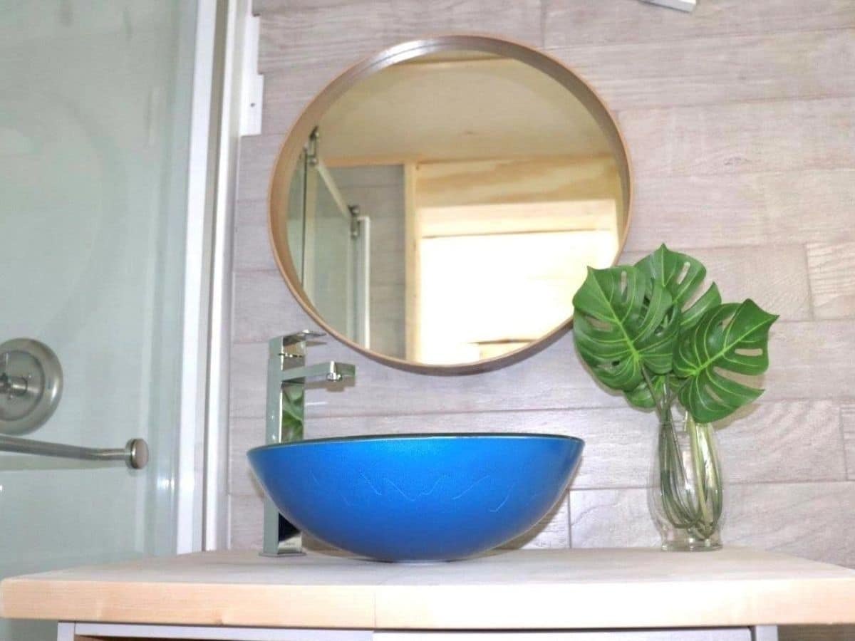 blue bowl sink below round mirror against gray wall