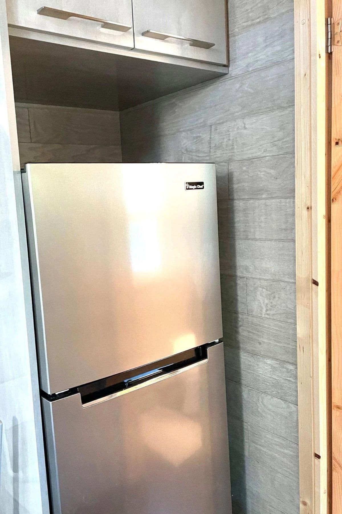 stainless steel refrigerator between walls in kitchen