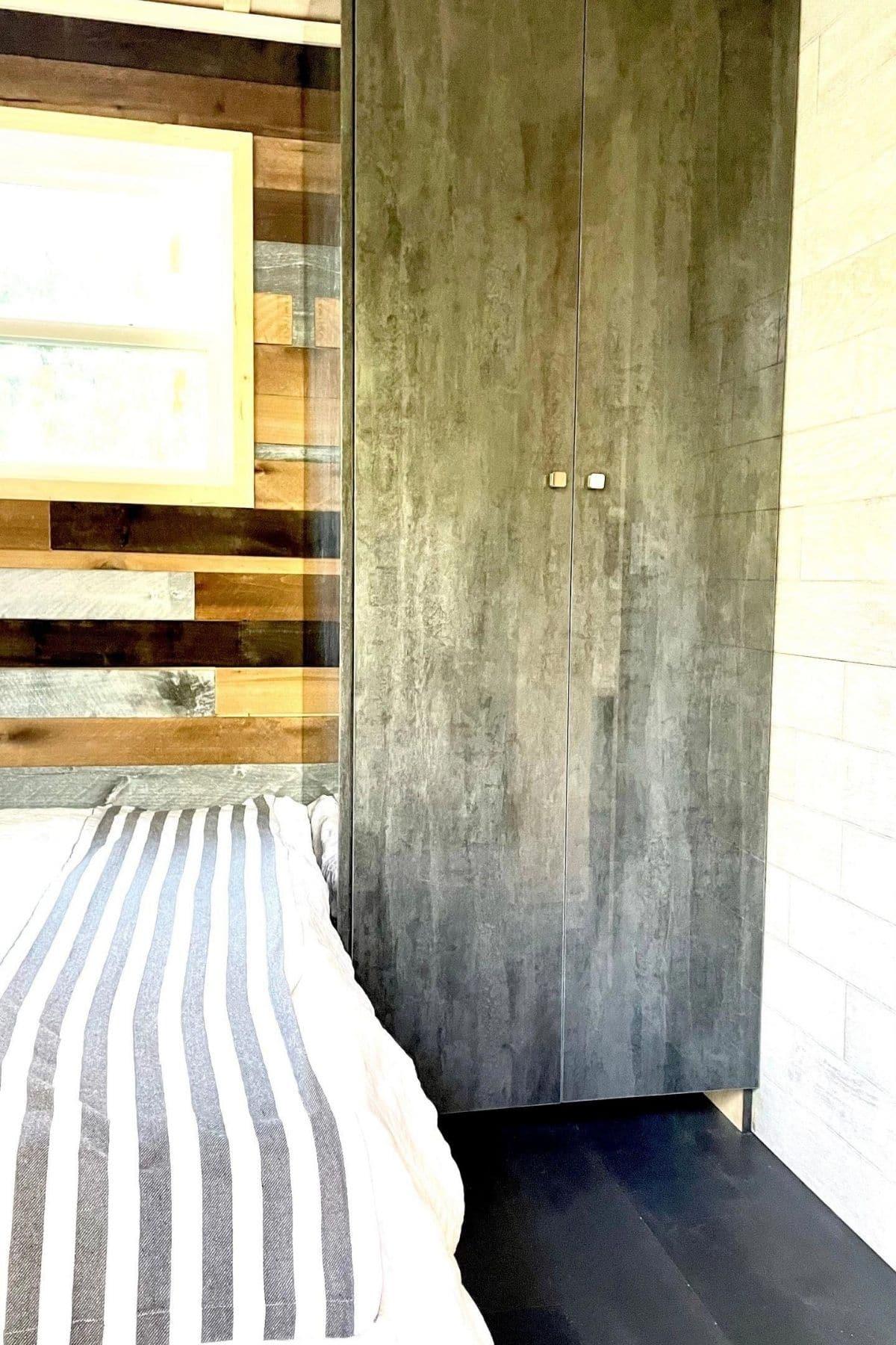 gray wood wardrobe beside bed