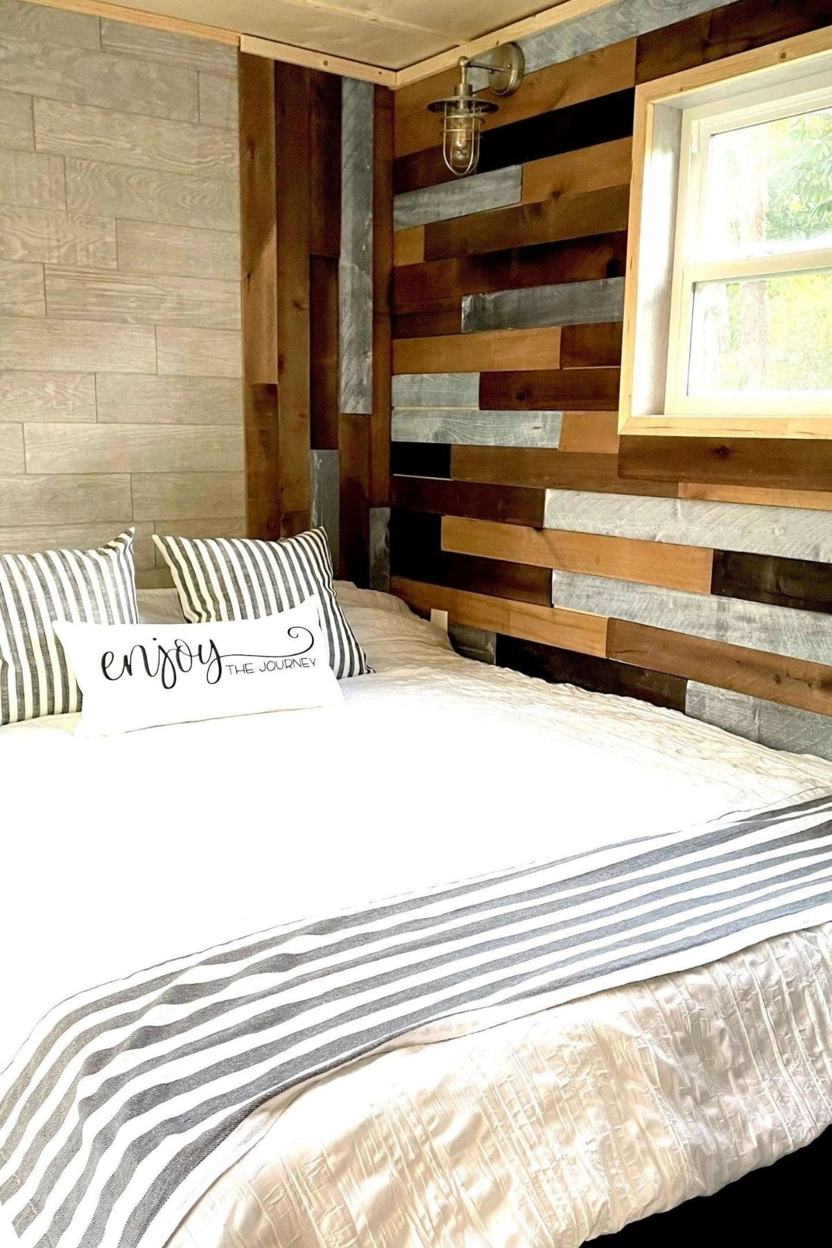 white and gray striped linens on bed next to reclaimed wood wall with window