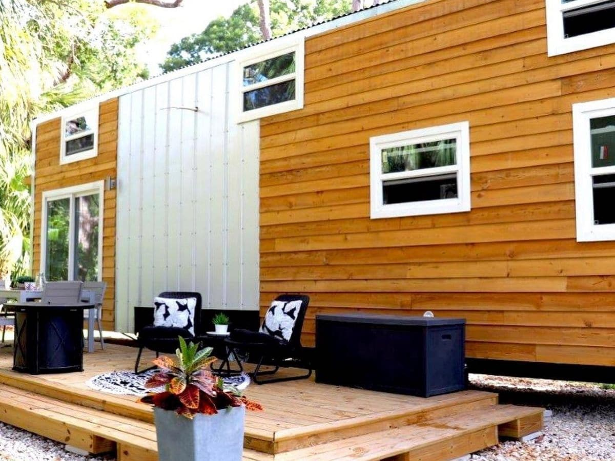 side of tiny home with wood siding and white trim