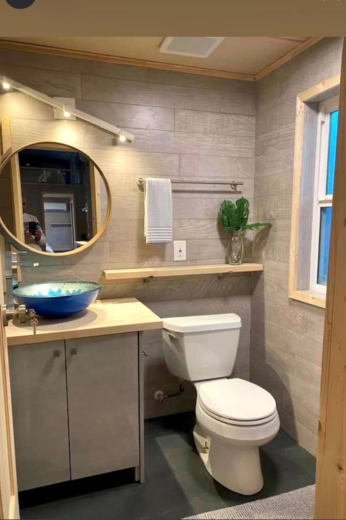 bathroom with light gray walls and light wood accents with blue bowl sink next to white flush toilet