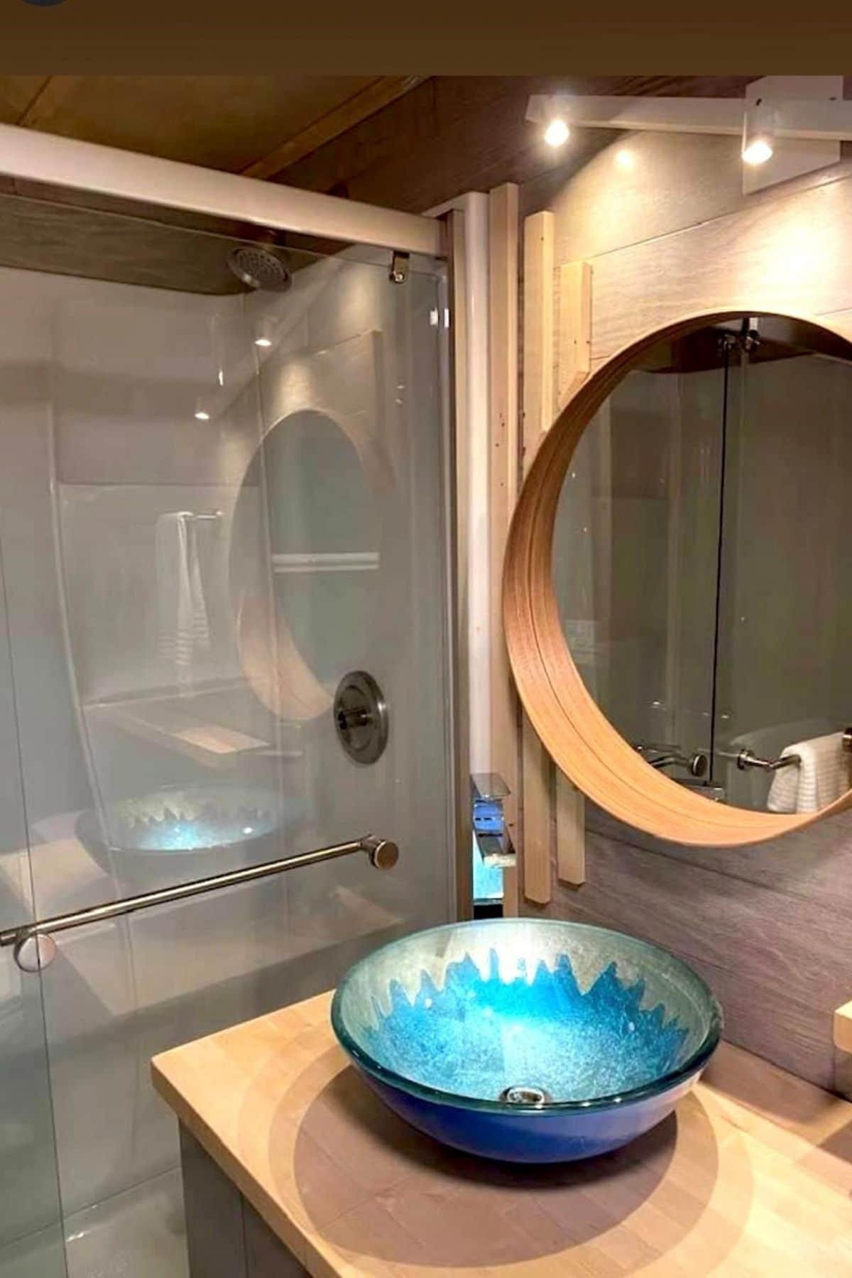 glass shower door next to blue bowl sink and round mirror