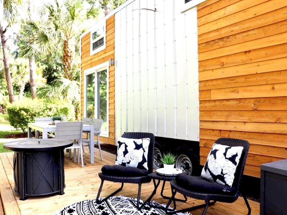 black chairs on porch in front of tiny home with wood siding and white accents