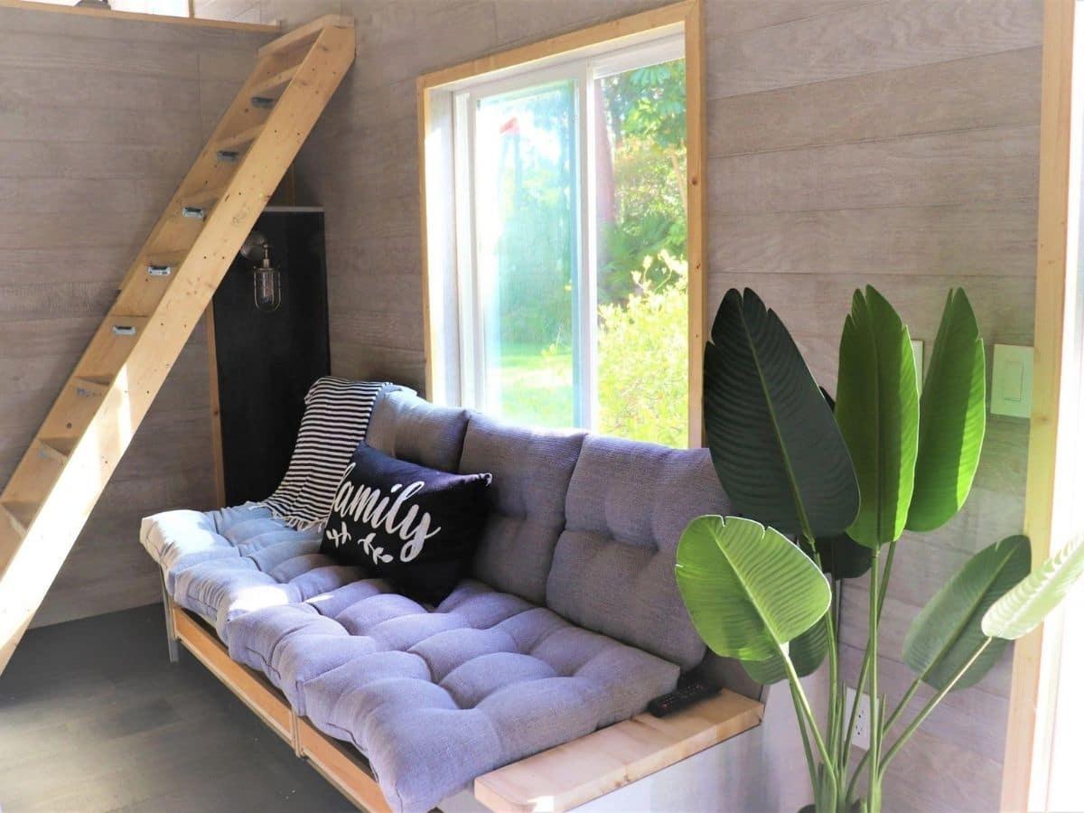 gray cushion futon on wood frame under windows