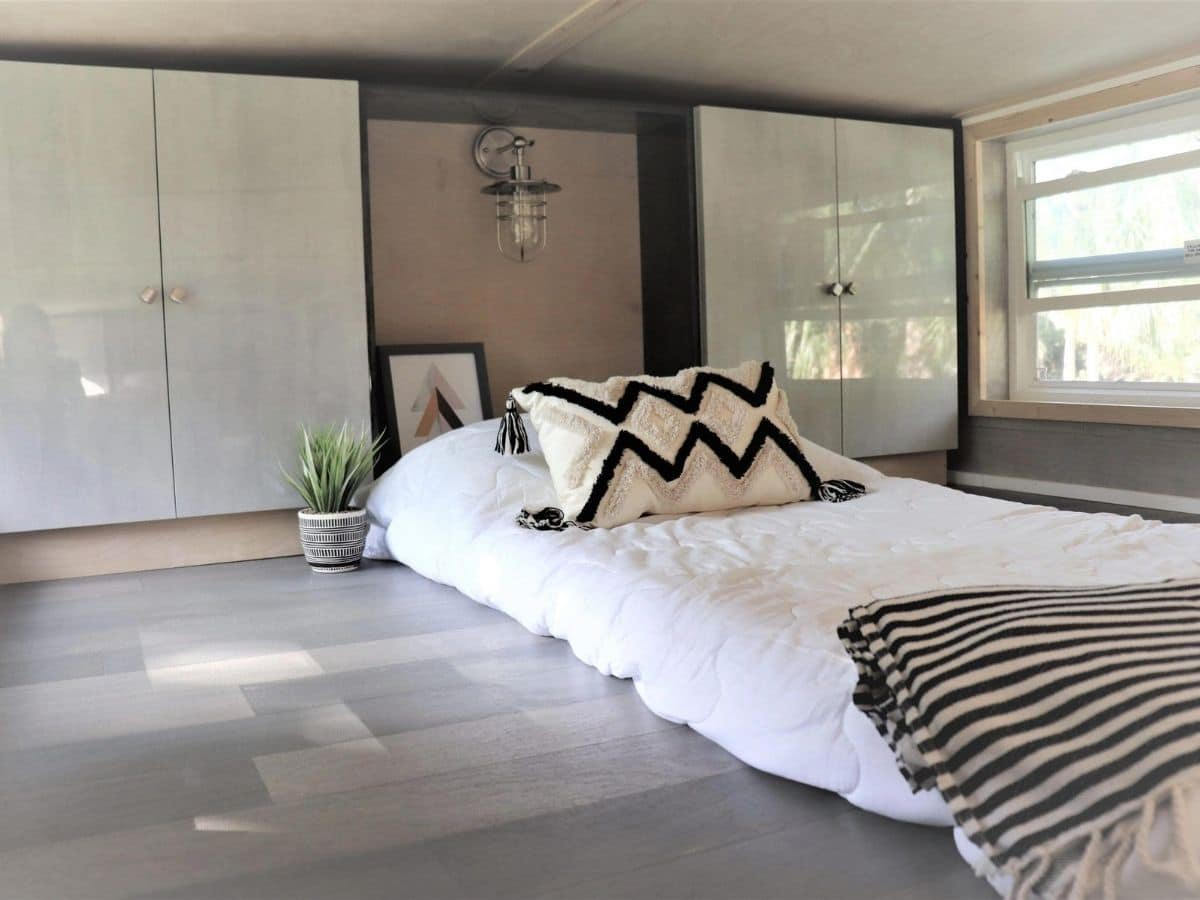 twin mattress with white bedding in center of loft