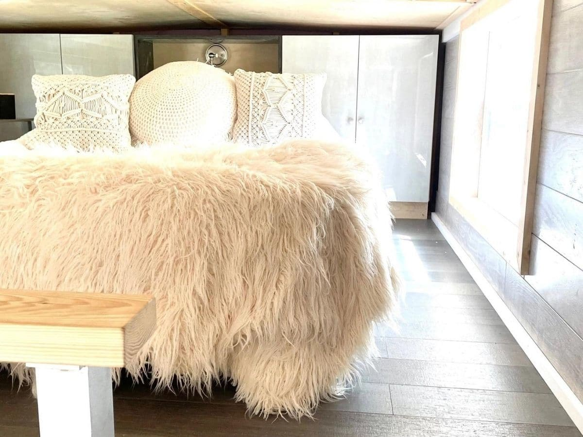 furry bedding on queen bed in loft with white cabinets in back