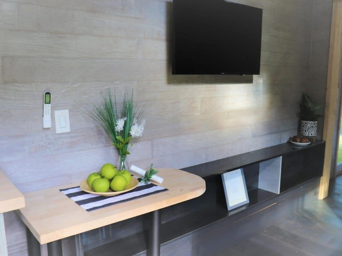 wood shelf underneath television on gray wall