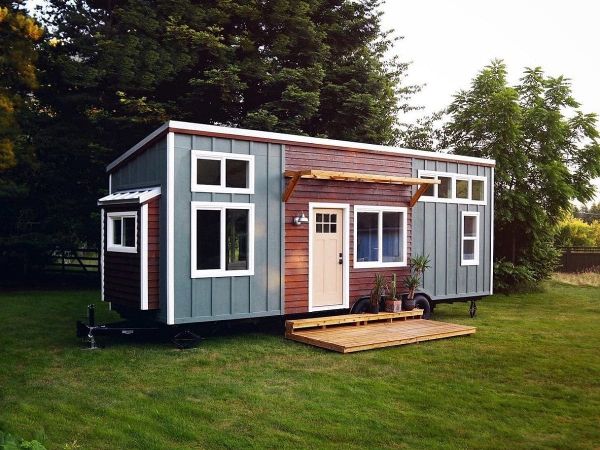 light blue tiny home with wood accent around white door on grass