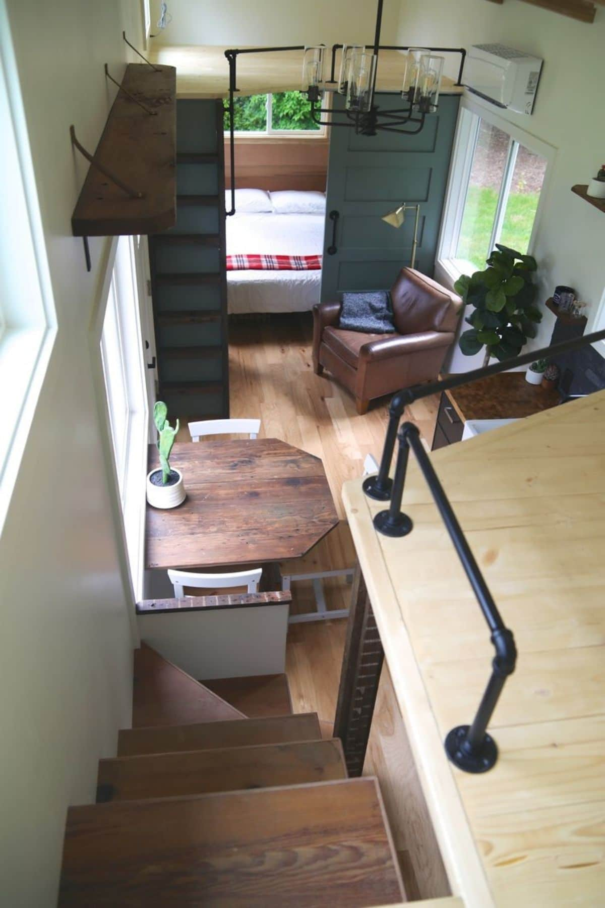 view down into tiny home from loft showing dining nook on left