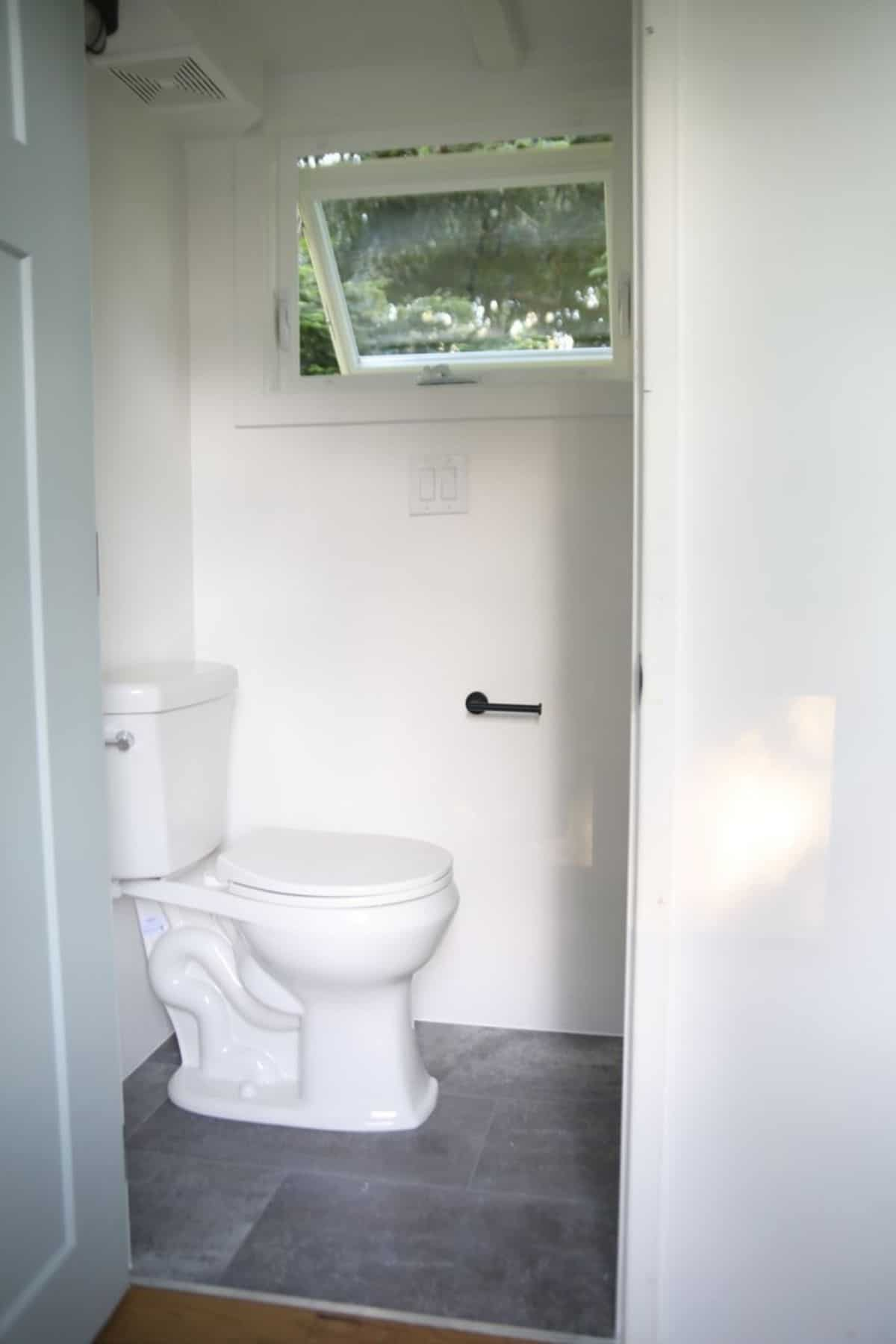 white flush toilet against white wall with window open above