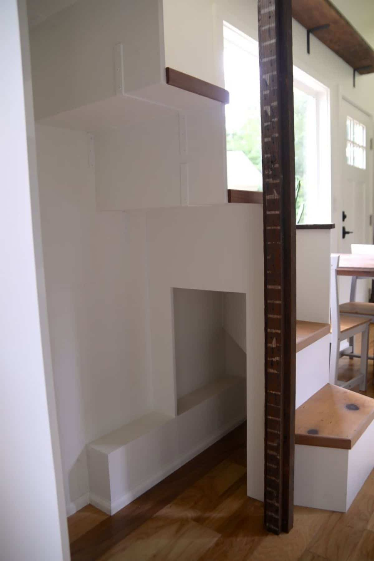 open storage beneath white stairs to loft in tiny house