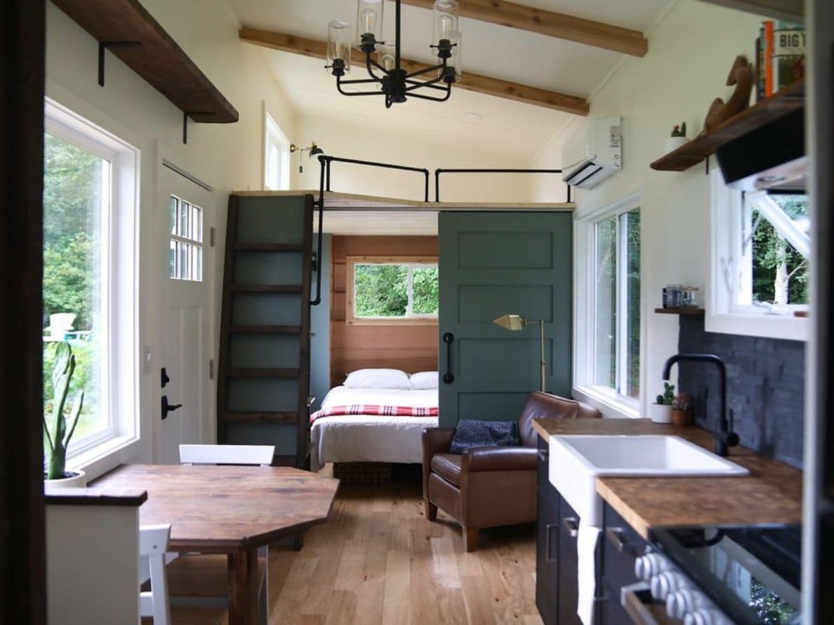 green barn door at end of room with green stairs to loft above bedroom