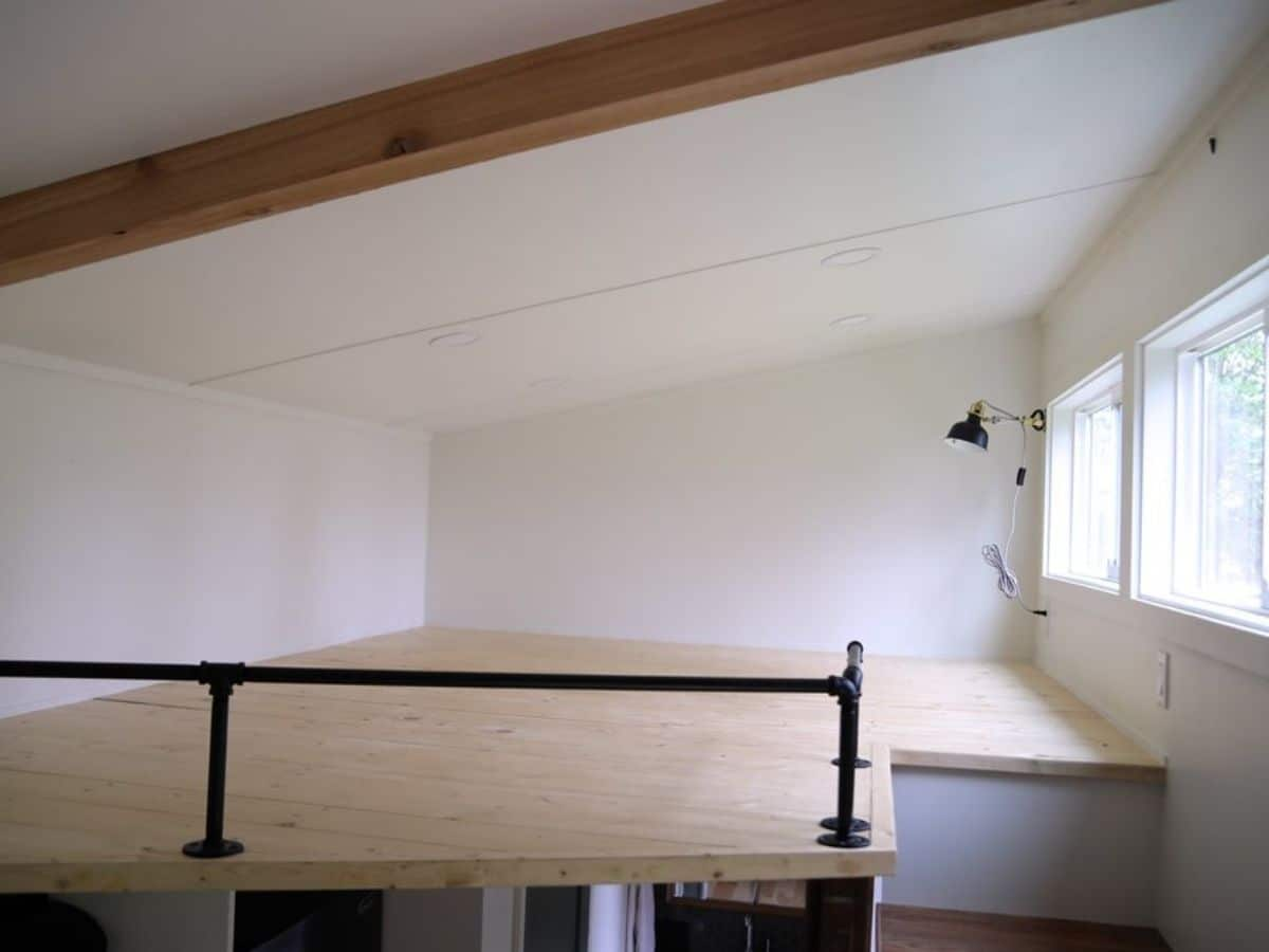 light wood floor in loft with white walls and window on right