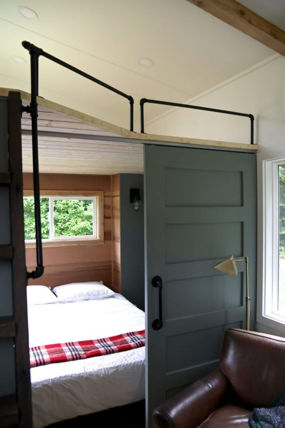 olive green barn door open under loft to show bed with plaid blanket at end