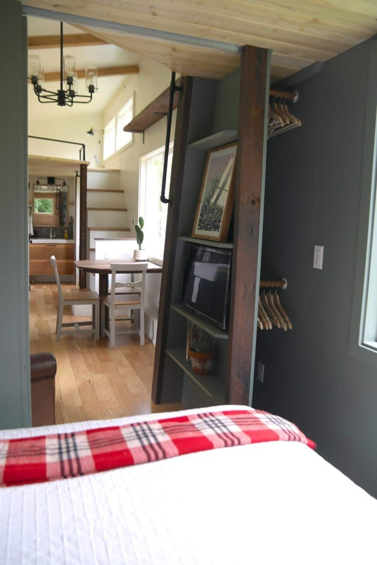 view into tiny home living room from tiny bedroom with bookcase by door